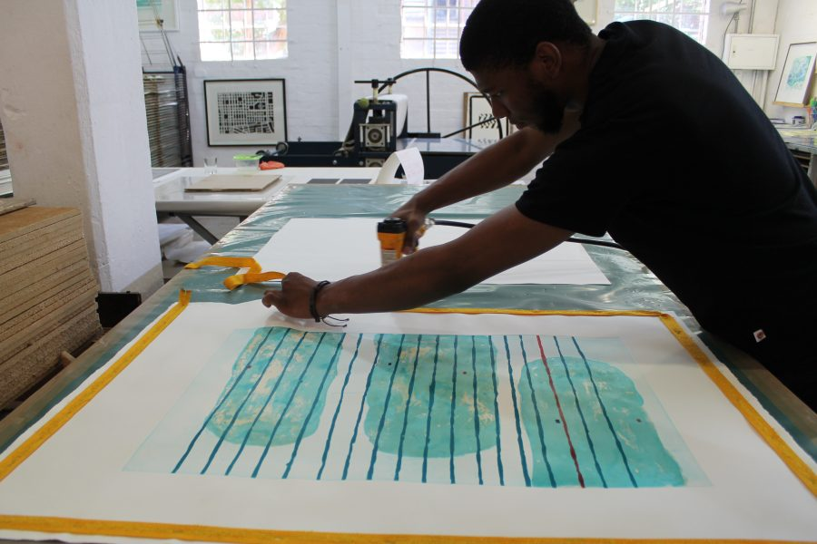 Step 3: Sbongiseni staples the print down. Once dried and flattened, the work will be cropped and framed.