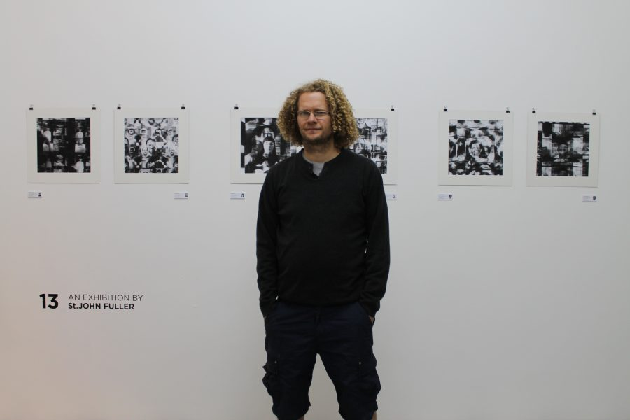 "St. John Fuller with his exhibition ""13"" in the background."