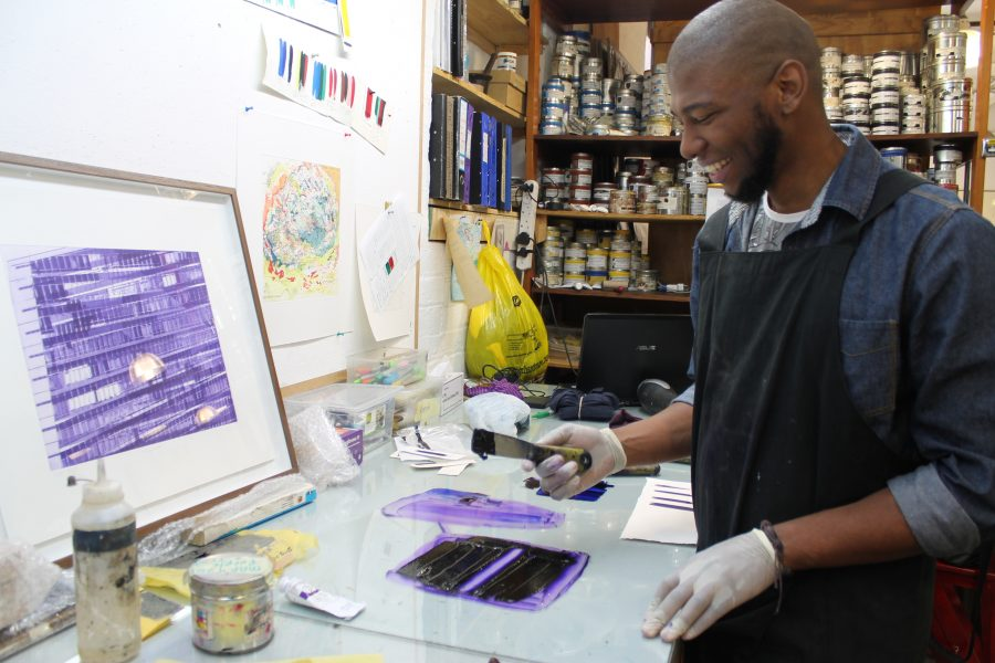 "Sbongiseni mixes his inks opposite a framed edition of ""Misregistered"" by Mary Wafer."