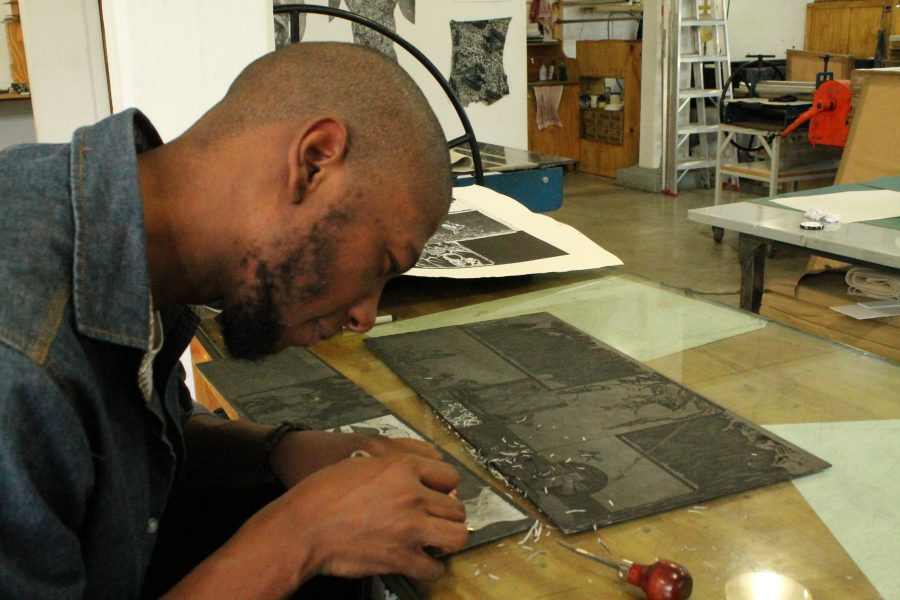 Sbongiseni demonstrates how to carve into a linocut. Here, he is creating the effect of thick, moving flames.