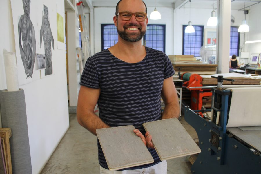 "Alonzo-Barkigia holdingup his lino plates. He explains: ""I attached these plates to the bottom of my shoes and walked 5km across Johannesburg. I'm very curious to see the results."" So are we – stay tuned and all will be revealed on his return to AOM in a couple weeks."