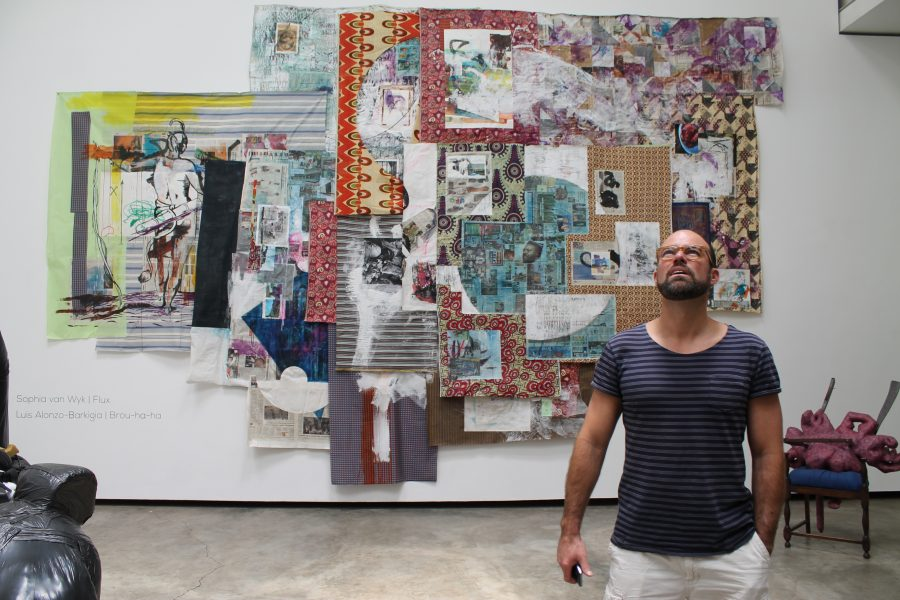 Alonzo-Barkigia in front of his giant collage and ink piece, Untitled (2015).