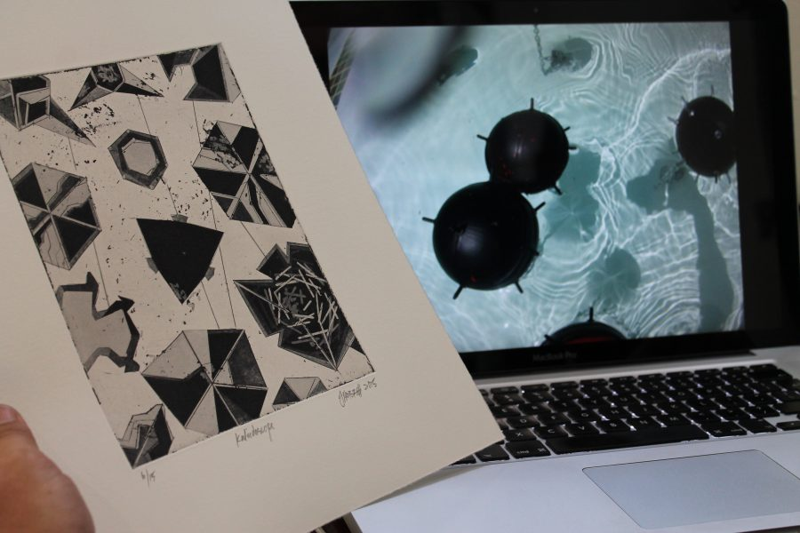 Hobbs holds Kaleidoscope up against a still from his contact mine set to contextualize his ideas for the etching.