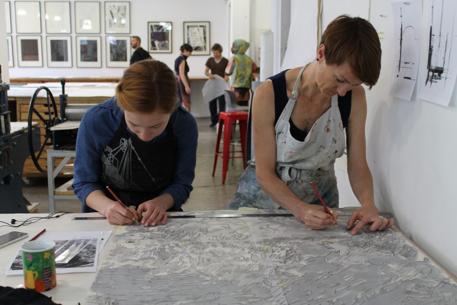 Robyn Penn (right) etches large cloud print.