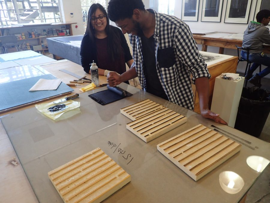 DKW printer Sbongiseni Khulu and RISD Joanna Cortez ink up the woodblocks to layer on the cardorandum print